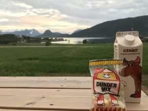 Dunder Mix candies and chocolate milk on a picnic table with the fjord scenery in the background