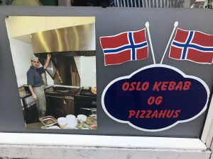 sign outside restaurant with chef and norwegian flag